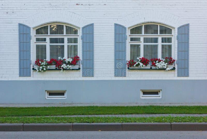 Pared blanca con dos ventanas y flores imagenes de archivo