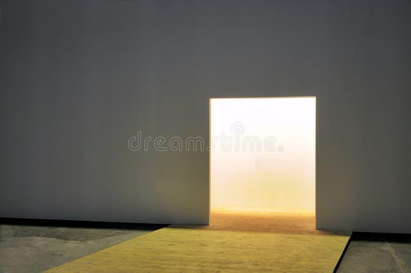 Pared blanca con la entrada abierta al espacio vacío luminoso imagen de archivo