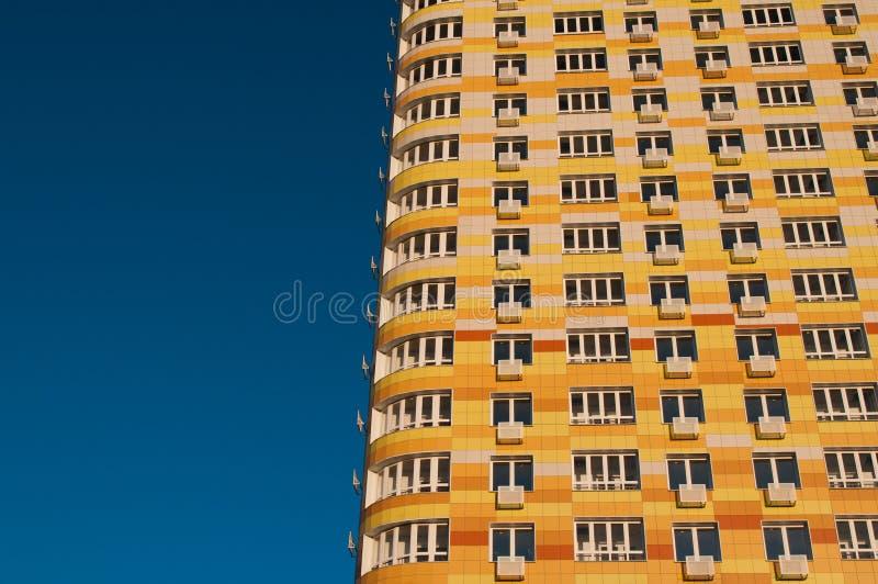 Pared con el nuevo edificio residencial de varios pisos moderno de los balcones en un fondo del cielo azul, fotos de archivo libres de regalías