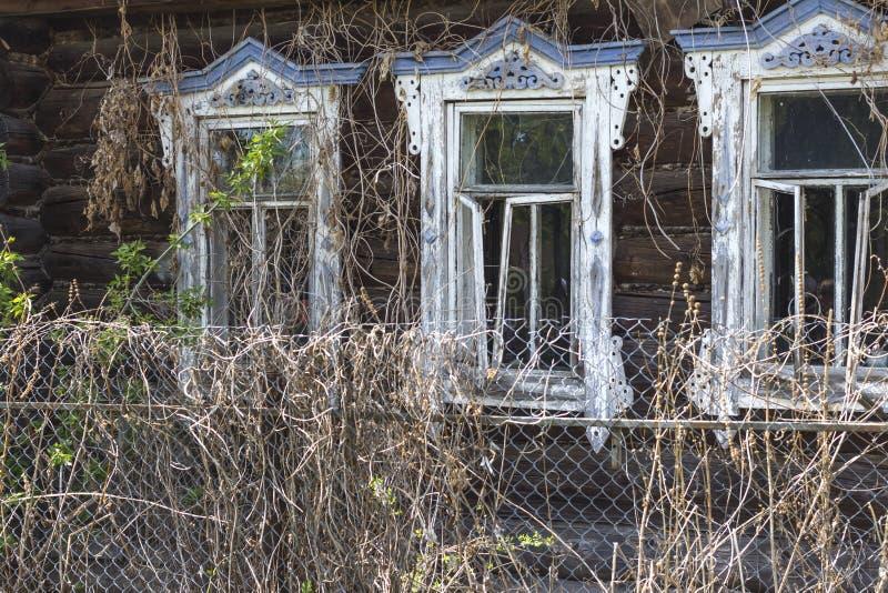 Pared con las ventanas de una casa de madera vieja Casa de madera destruida abandonada imagenes de archivo