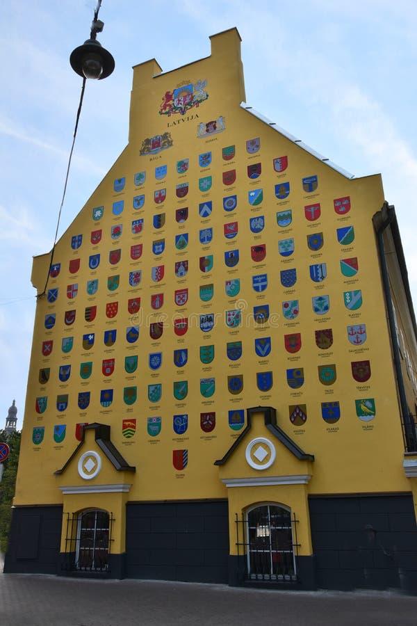 Pared con los escudos de armas de las ciudades letonas en Riga foto de archivo libre de regalías