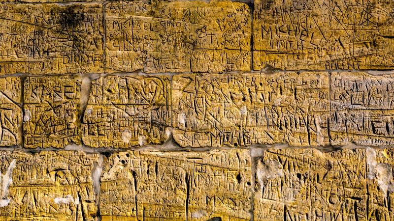 Pared con los ladrillos de la piedra caliza con los grabados ilegibles que han sido escritos por la gente con el paso del tiempo imagen de archivo libre de regalías