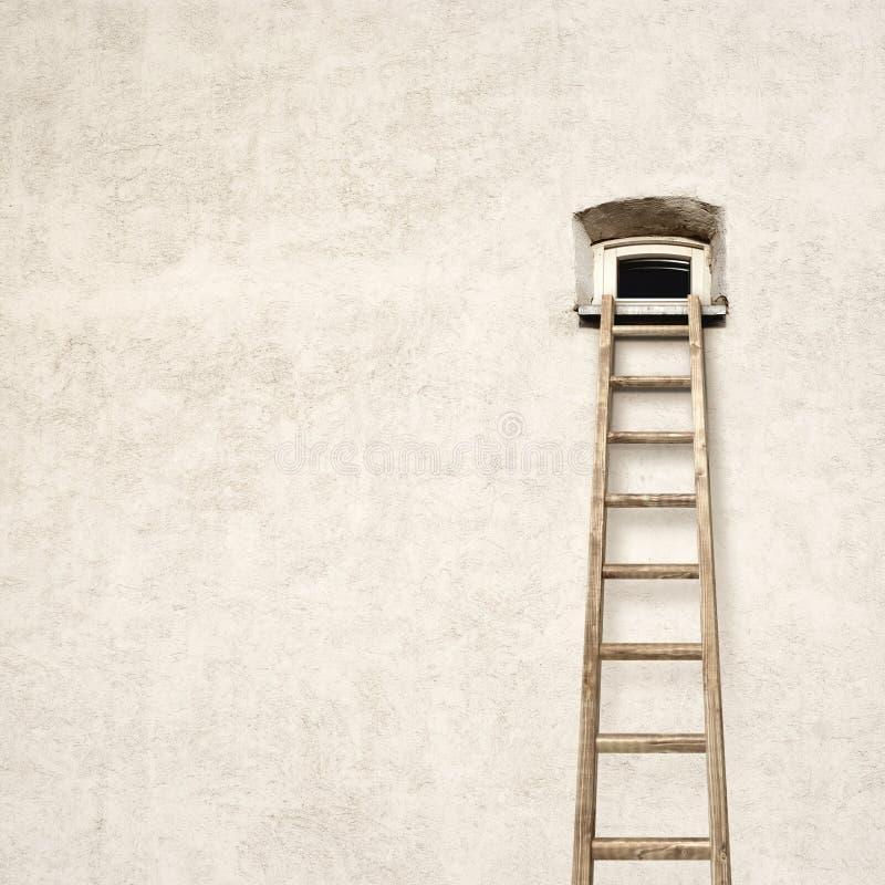 Pared con una pequeña ventana y una escalera de madera fotografía de archivo libre de regalías