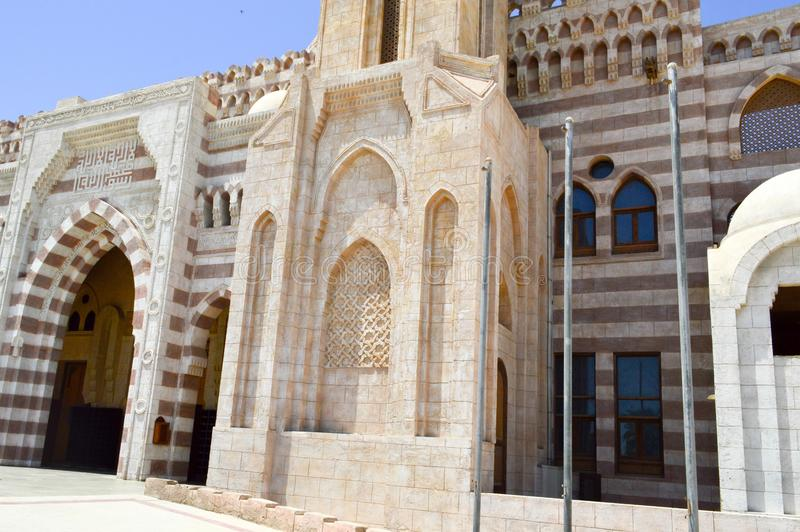 Pared con una textura hermosa de una mezquita árabe islámica musulmán hecha de la arquitectura blanca del ladrillo con los arcos, imagen de archivo