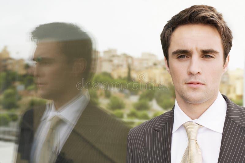 Pared confiada de Standing By Glass del hombre de negocios imagen de archivo