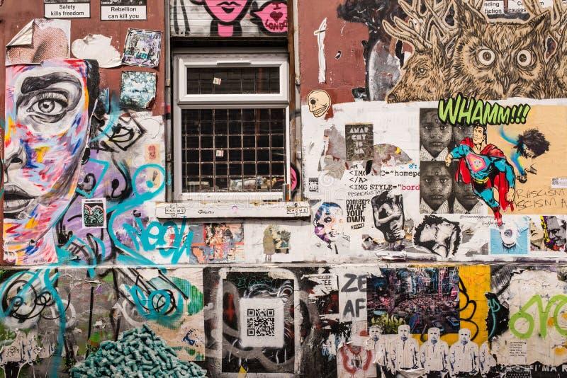 Pared cubierta en murales de la pintada y del papel pintado imagen de archivo
