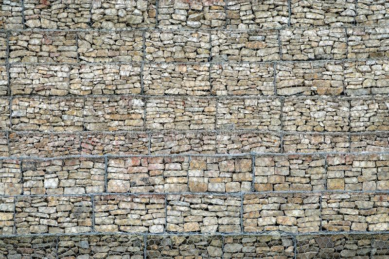 Pared de Gabion de rocas y de piedras en caja del alambre de metal Cerca de piedras en la rejilla Pared de piedra protectora en l imágenes de archivo libres de regalías