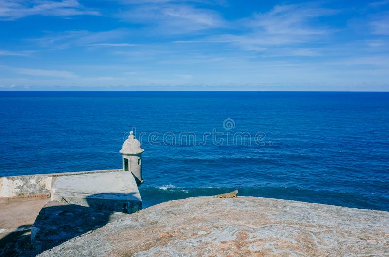 Pared de la fortaleza y caja de centinela sobre el mar azul en San Juan viejo, Puerto Rico foto de archivo