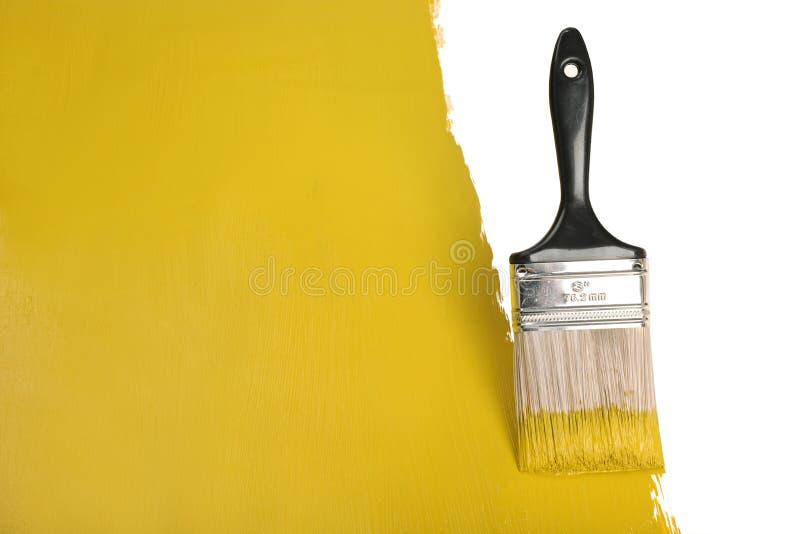 Pared de la pintura del cepillo con la pintura amarilla foto de archivo libre de regalías