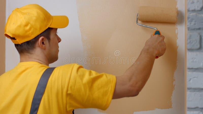 Pared de la pintura del trabajador joven dentro foto de archivo