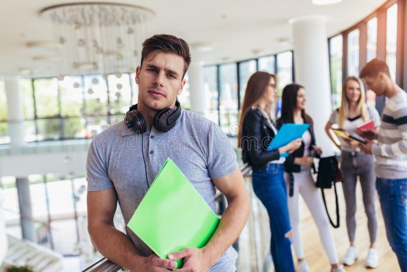 Pared de la situaci?n del estudiante masculino en pasillo de una universidad Estudiante masculino cauc?sico en campus universitar fotos de archivo