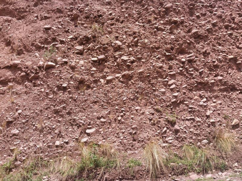 pared de la suciedad con las rocas que se pegan hacia fuera imágenes de archivo libres de regalías