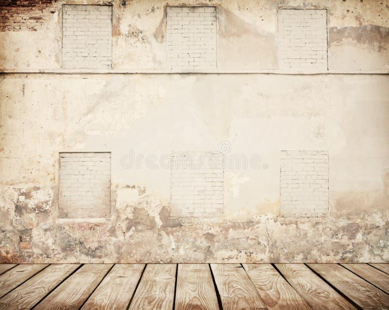 Pared de ladrillo agrietada con el piso de madera imagen de archivo