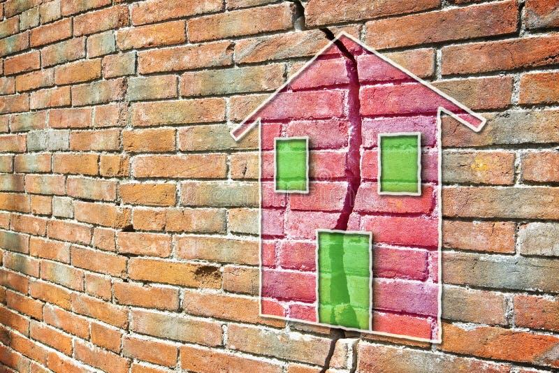 Pared de ladrillo agrietada con una casa coloreada dibujada en ella fotografía de archivo