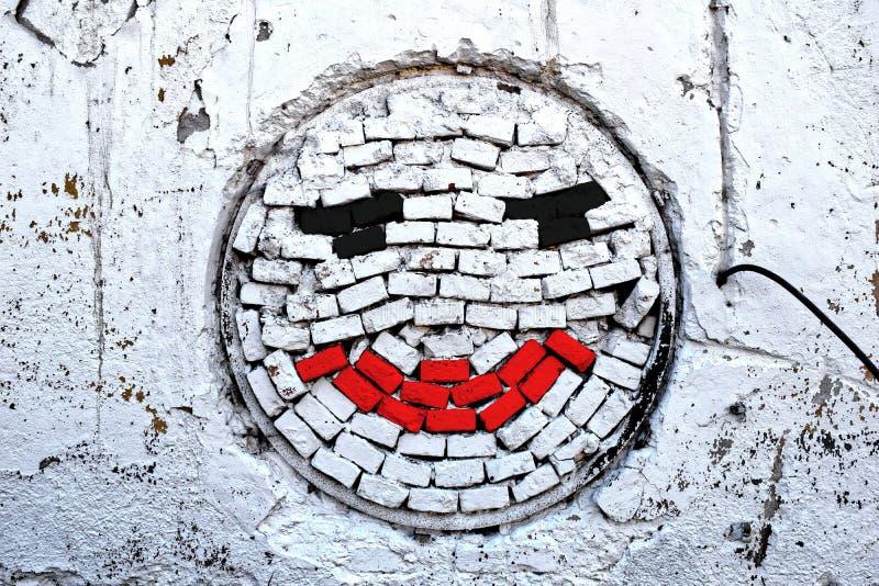 Pared de ladrillo blanca con sonrisa imagenes de archivo