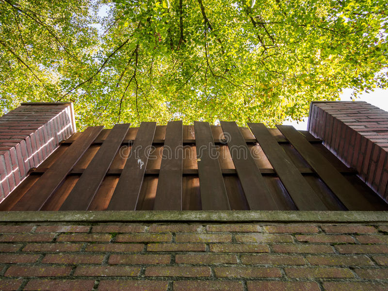 Pared de ladrillo, cerca y árboles foto de archivo libre de regalías