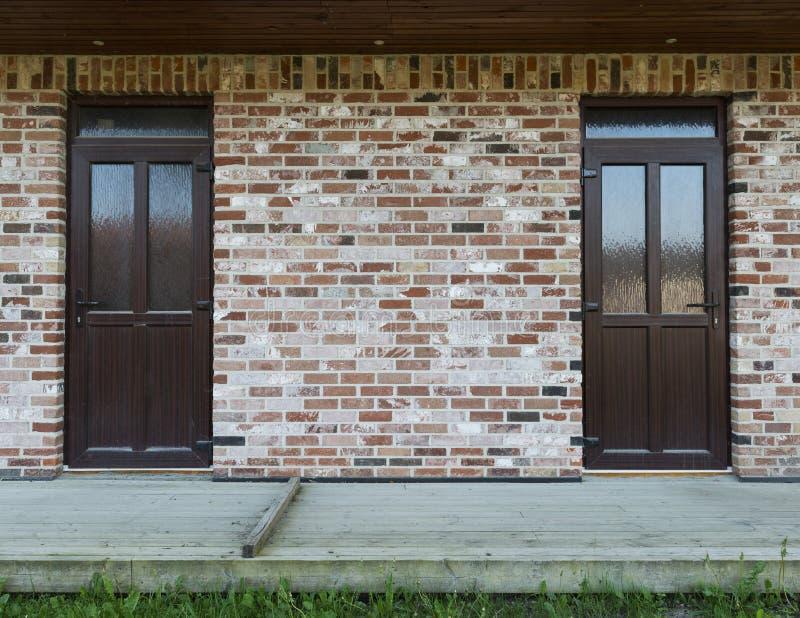 Pared de ladrillo con dos puertas, la terraza de madera y la hierba fotografía de archivo