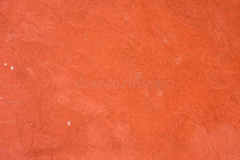 Pared de ladrillo, pared enyesada, superficie áspera, rojo pintado Las paredes adornan los edificios exteriores que se pintan roj fotos de archivo