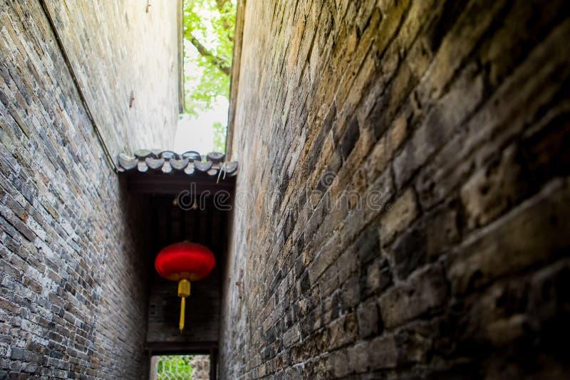 Pared de ladrillo estrecha con la lámpara roja china, pared antigua del parque del pueblo de China foto de archivo libre de regalías