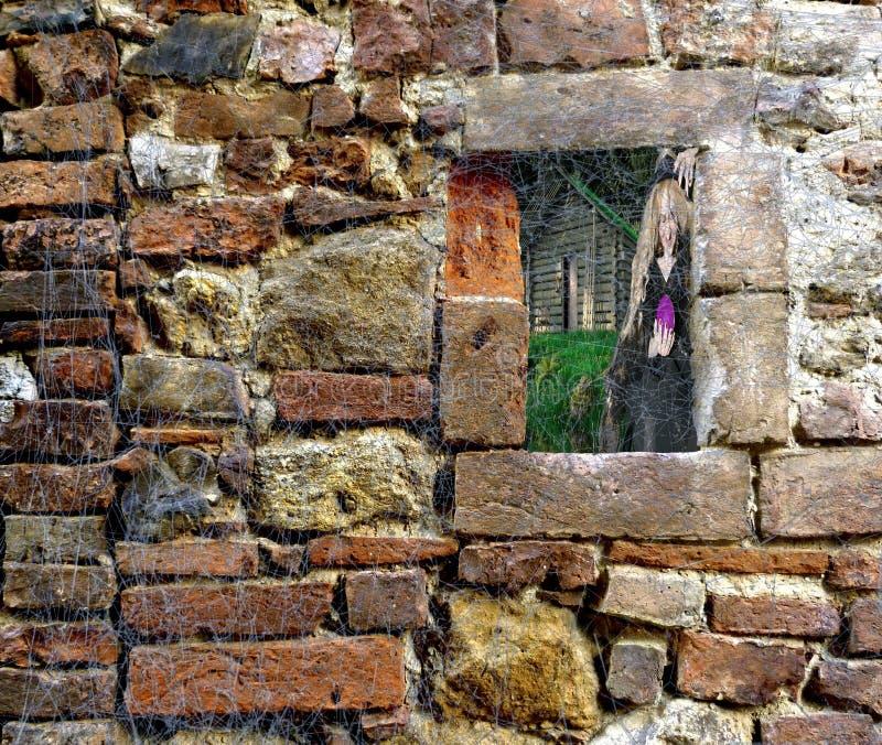 Pared de ladrillo de Halloween cubierta en trapos del web de araña con la ventana que mira en una cabina y una bruja del bosque foto de archivo