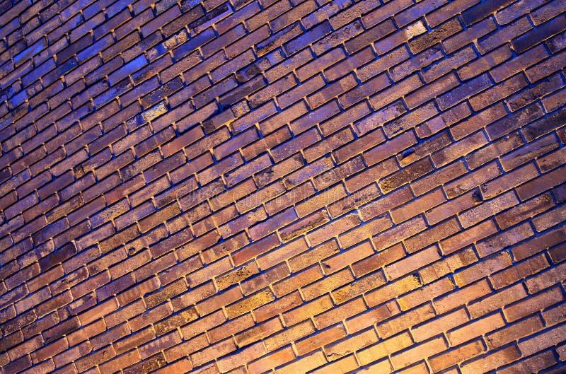 Pared de ladrillo multicolora con la iluminación en la noche, fondo, posición diagonal imagen de archivo
