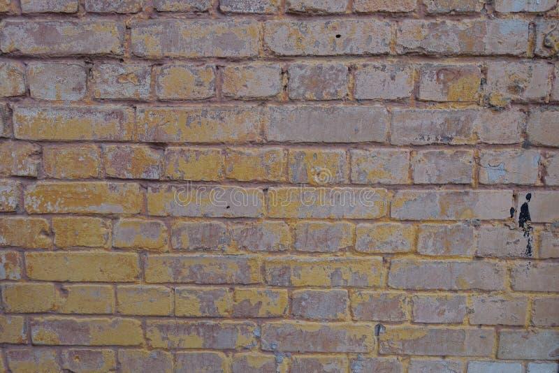 Pared de ladrillo pintada marrón y amarilla rosácea pálida fotos de archivo