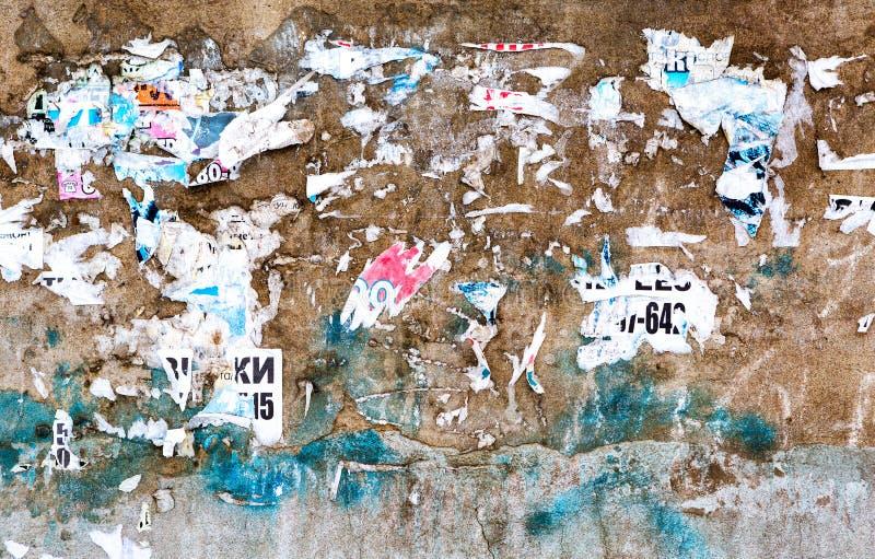 Pared de ladrillo resistida del grunge con los pedazos del papel viejo como detrás fotografía de archivo