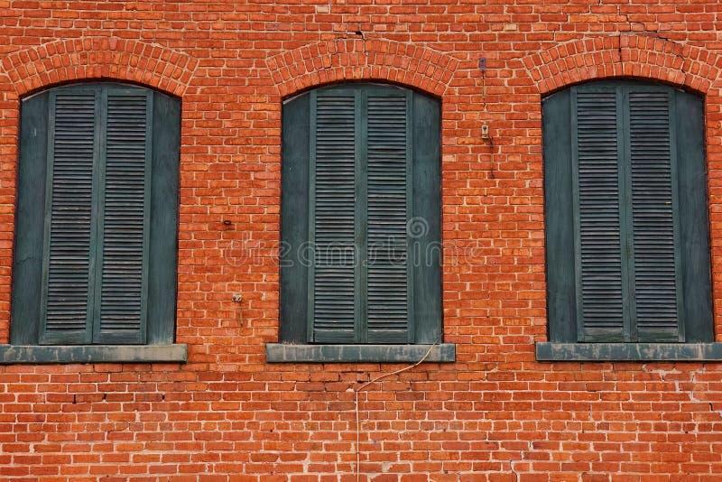 Pared de ladrillo roja con tres ventanas verdes de madera imagen de archivo libre de regalías
