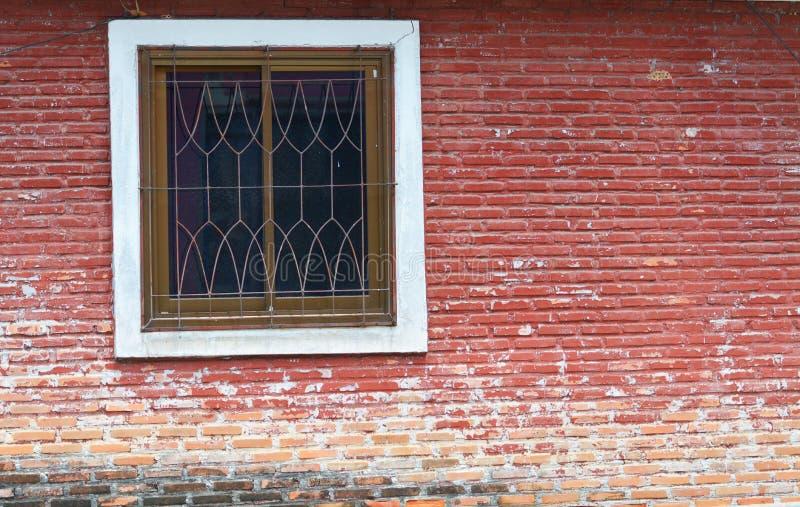 Pared de ladrillo roja con una ventana foto de archivo