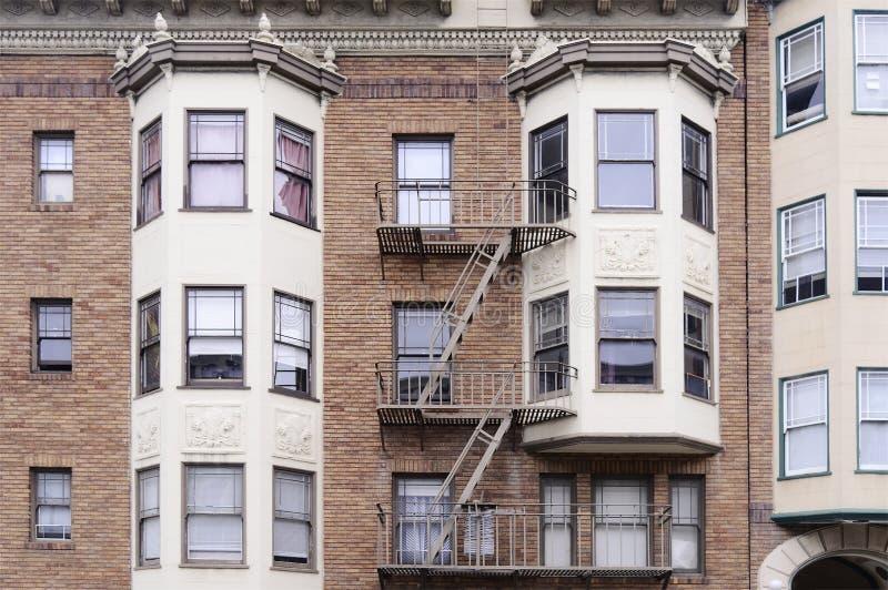 Pared de ladrillo roja moderna con muchas ventanas fotos de archivo