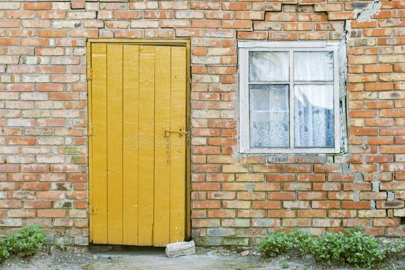 Pared de ladrillo roja, puerta de madera y ventana fotos de archivo