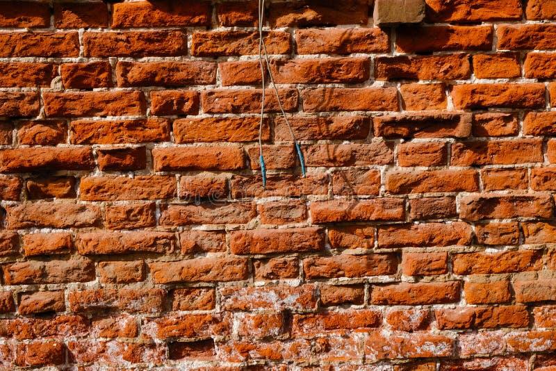 Pared de ladrillo roja resistida vieja como fondo con dos alambres colgantes imagen de archivo
