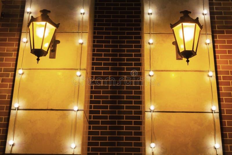 Pared de ladrillo roja vieja con dos proyectores Luz alrededor primer de la textura del fondo foto de archivo