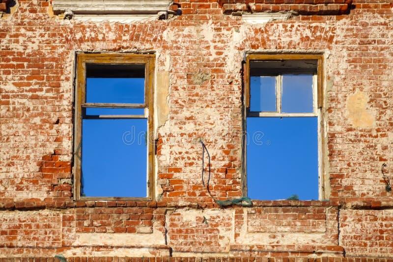 Pared de ladrillo roja vieja con dos ventanas imagenes de archivo