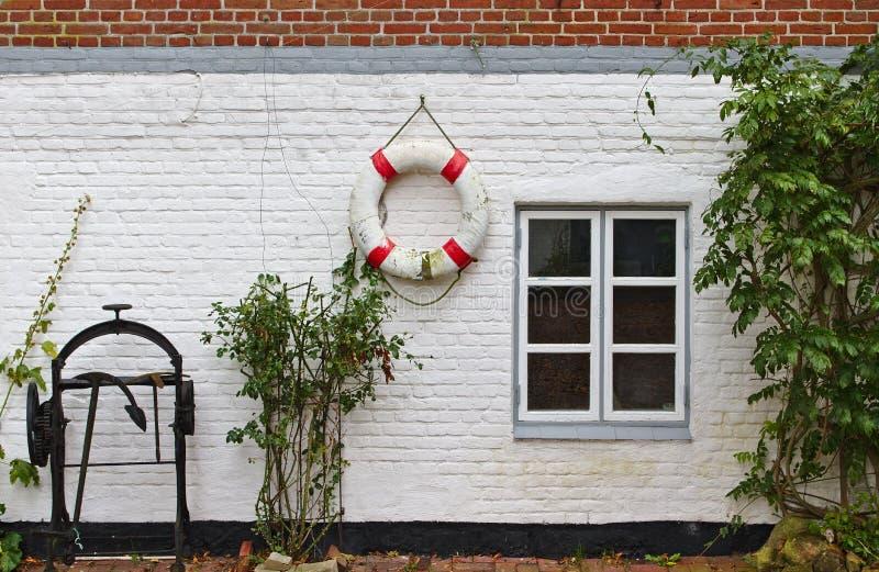 Pared de ladrillo roja y blanqueada con la ventana, arbustos verdes, boya de vida roja y blanca y torno histórico del ancla foto de archivo libre de regalías