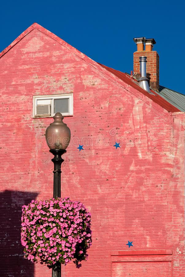 Pared de ladrillo rosada, tubo rosado de la chimenea de la flor, polo ligero de calle y cielo azul bajo luz del sol en Georgetown imágenes de archivo libres de regalías