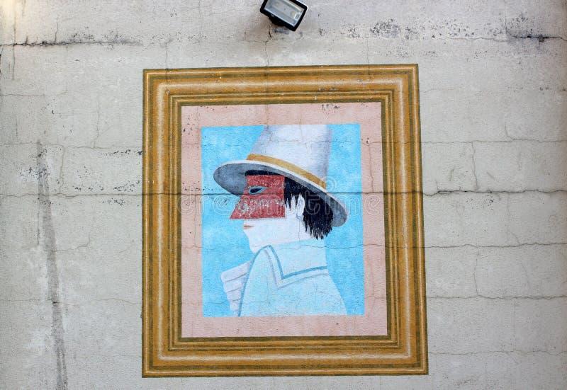 Pared de ladrillo vieja con el arte enmarcado de la calle del hombre en la máscara, Austin Texas, 2018 imagen de archivo libre de regalías