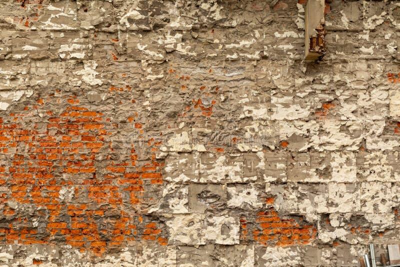 Pared de ladrillo vieja con yeso y hormigón destruidos Desmontar el edificio imagen de archivo