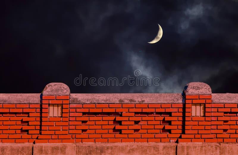 Pared de ladrillo vieja debajo del cielo nocturno imagenes de archivo