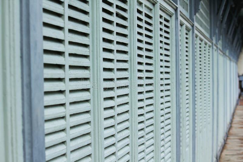 Pared de madera con gris y una pequeña abertura para la ventilación imagenes de archivo