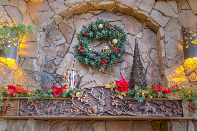 Pared de piedra adornada con los ornamentos de la Navidad que encantan y las luces calientes foto de archivo