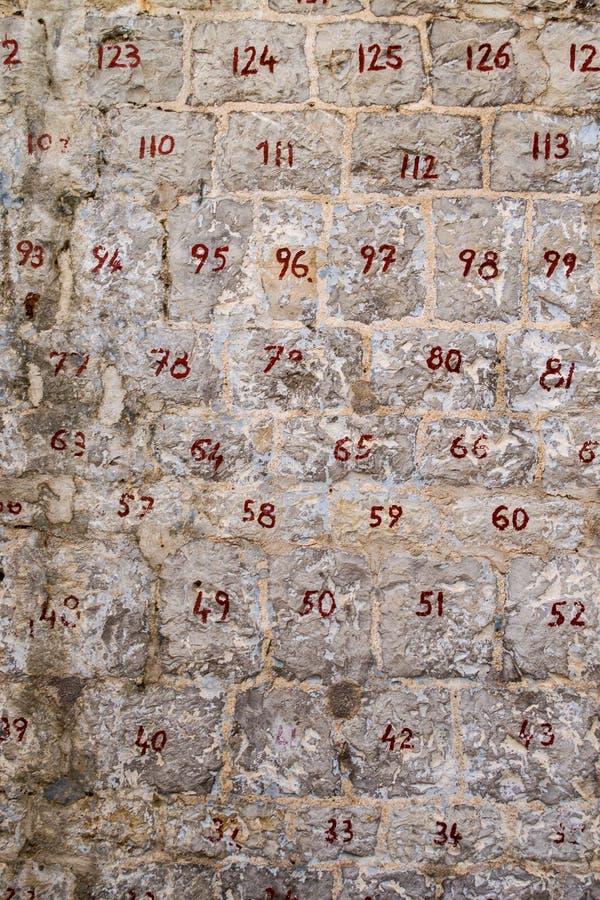 Pared de piedra con las piedras numeradas Números rojos de dos dígitos en las piedras Restauración de la pared foto de archivo