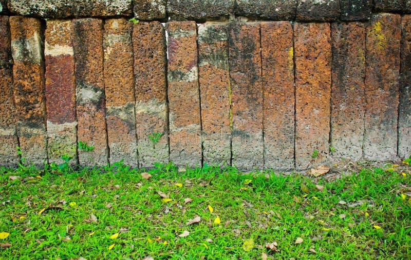 Pared de piedra del bloque con la hierba fotografía de archivo