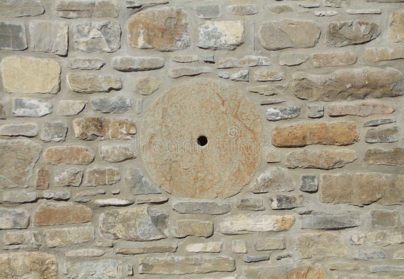 Pared de piedra en colores calientes con la muela abrasiva foto de archivo