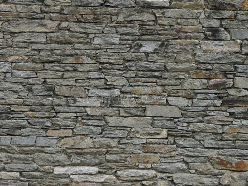Pared De Piedra En Colores Grises. Azulejos cortados de piedras para dar apariencia de ser bloques, revestidos sobre una pared exterior stock photos