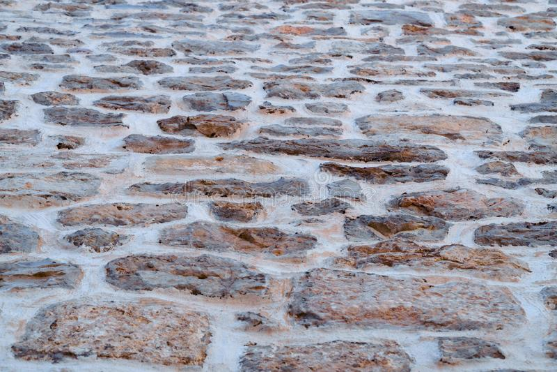 Pared de piedra en la calle n la tarde imagen de archivo