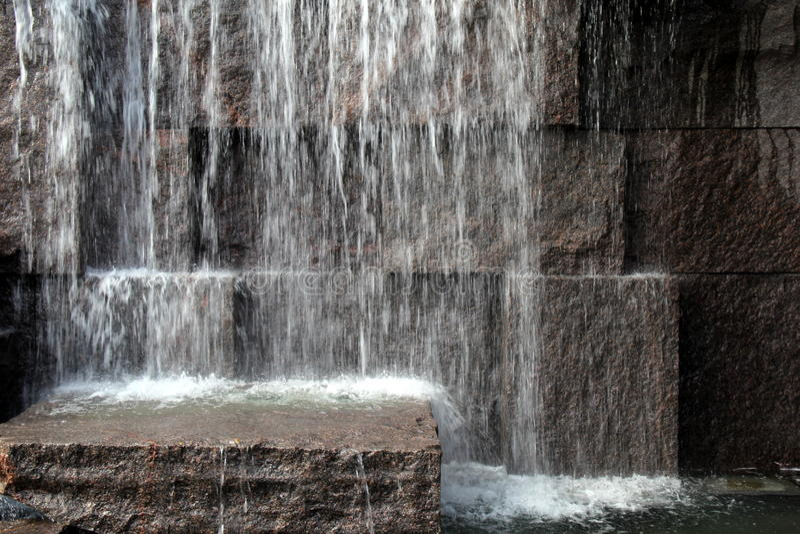 Pared de piedra grande con agua que salpica desde arriba fotos de archivo libres de regalías