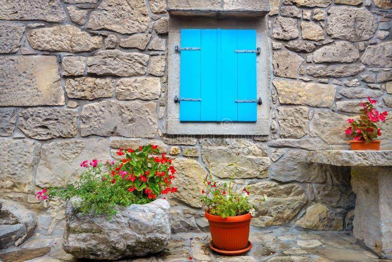 Pared de piedra de la casa vieja con la ventana y las flores azules en potes Ronquido, Croatia imagen de archivo libre de regalías