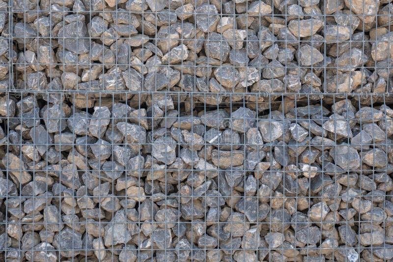 Pared de piedra sostenida por una rejilla del metal fotografía de archivo libre de regalías