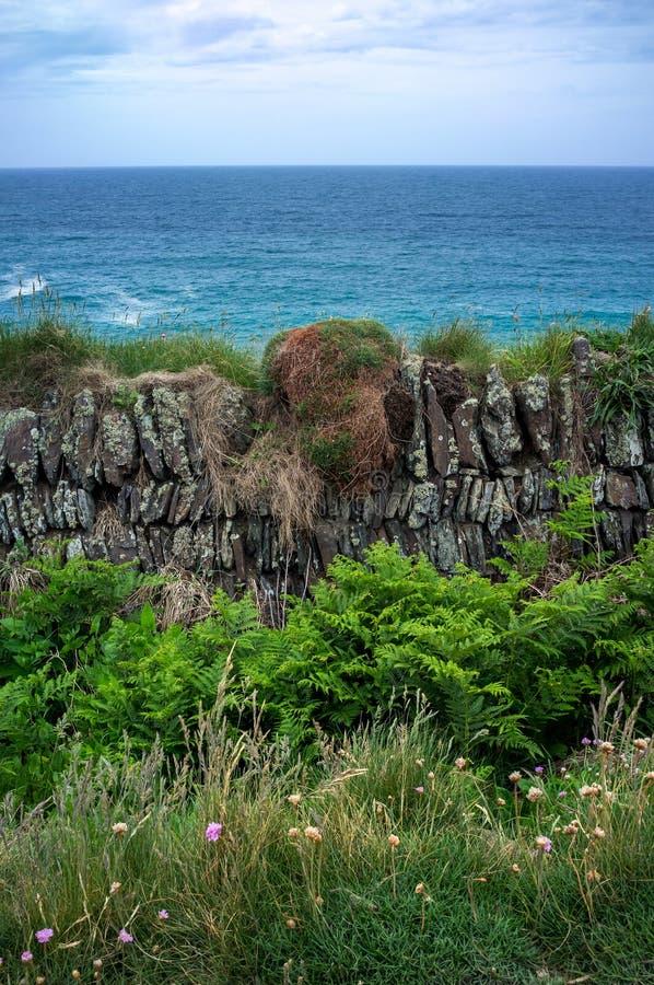 Pared de piedra vieja que pasa por alto el océano fotos de archivo